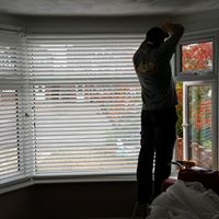Paul fitting a blind in a living room